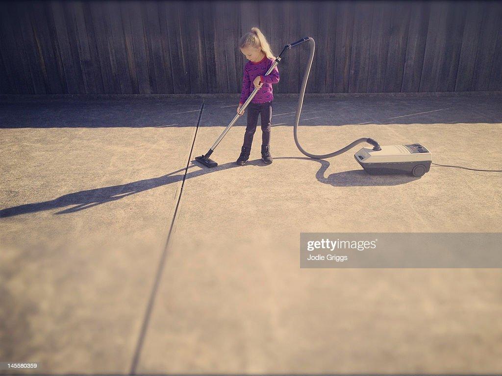 Child using vacuum cleaner outside on concrete : Foto de stock