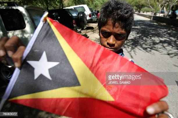 A child vendor displays an East Timor's national flag as he looks for customers along a beach in Dili 12 August 2007 The World Bank says East Timor...