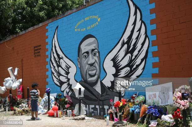 A child views a mural dedicated to George Floyd across the street from the Cuney Homes housing project in Houston's Third Ward where Floyd grew up...