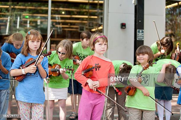 child violinists taking a bow with one girl looking unhappy - violin family stock photos and pictures