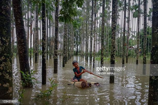 Child wades through a flooded area using a makeshift raft at Maulovir Para, Cox's Bazar on July 30, 2021 after monsoon floods and landslides have cut...