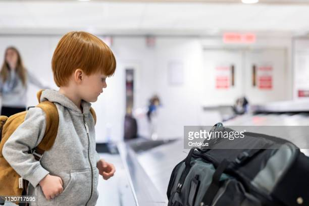 a child waiting for suitcase on conveyor belt in airport - luggage rack stock photos and pictures