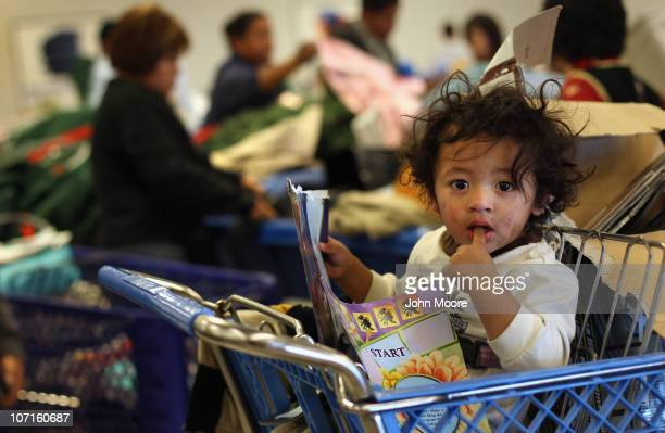 A child waits as his mother joins fellow lowincome shoppers searching bins for toys at a Goodwill thrift store on Black Friday November 26 2010 in...