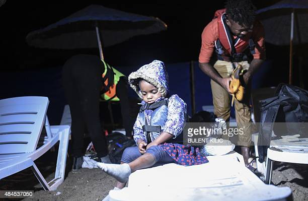 A child waits as migrants prepare to board a boat to reach the Greek Island of Kos from Turkish side Bodrum early on August 20 2015 The UN refugee...