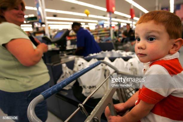 A child waits for his mother at the checkout counter of a WalMart Supercenter May 11 2005 in Troy Ohio WalMart America's largest retailer and the...