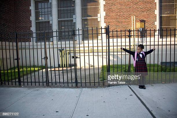 A child waits for the first day of school outside Public School 53 in the Bronx section of New York City on Tuesday September 4 2007