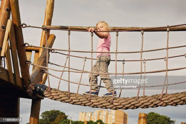 child walking across a rope bridge - southport england stock pictures, royalty-free photos & images