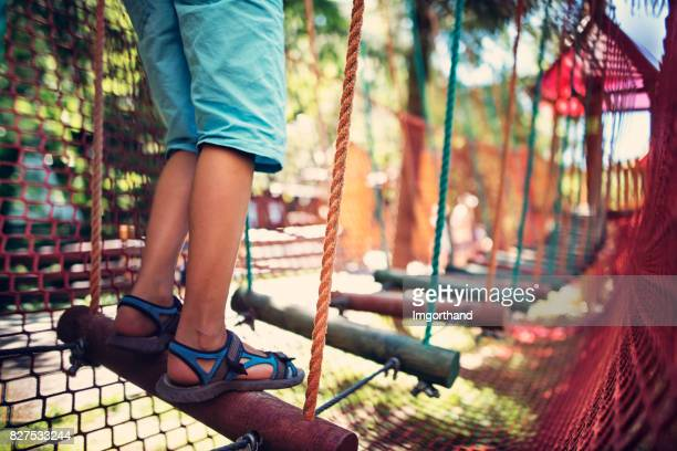 Child walking in modern ropes course playground