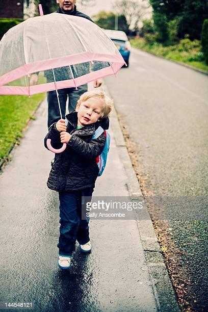 Child walking in rain with big umbrella