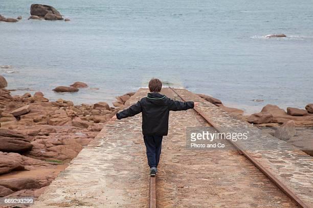 Child Walking On A Rail In Seaside