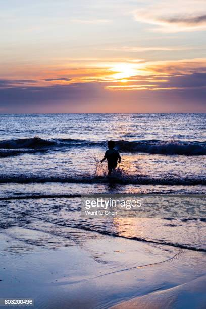 child walking on the beach at sunset