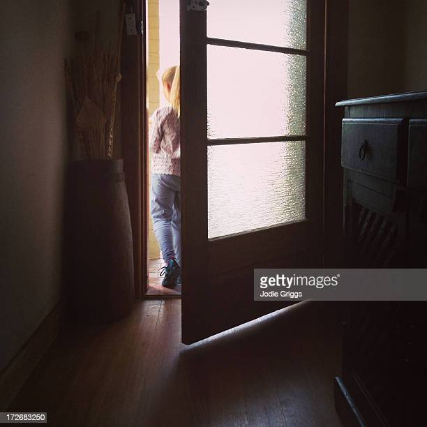 Child walking out door leaving a house