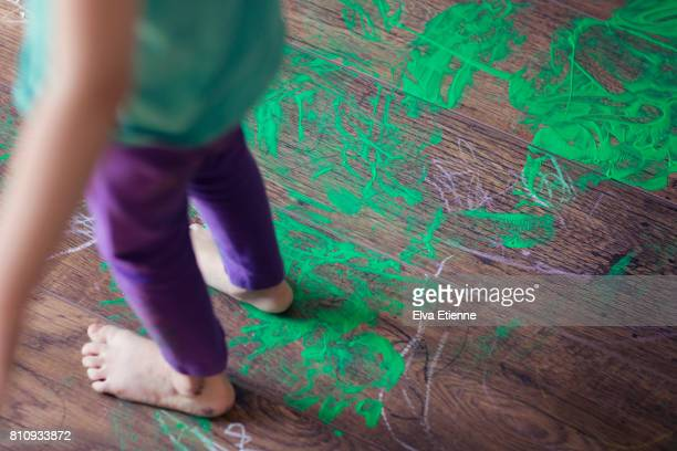 child walking through messy, spilt green paint on a wooden floor - innocence stock-fotos und bilder