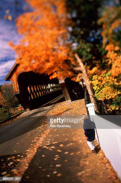 Child (2-4) walking towards covered bridge, autumn, Vermont, USA