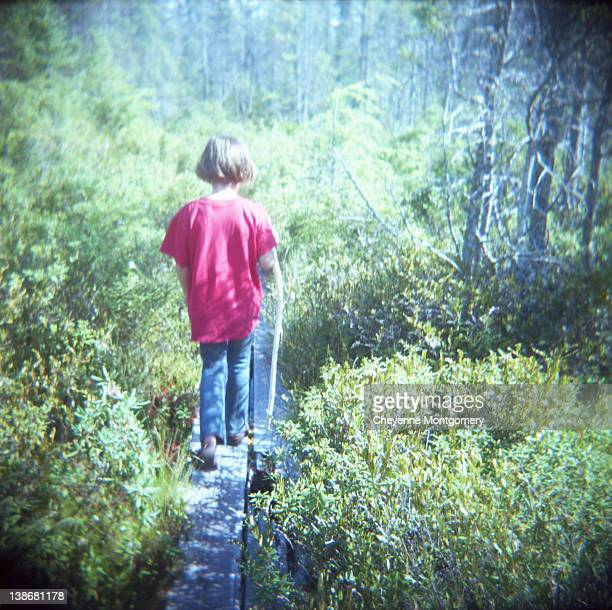 Child walking within trees