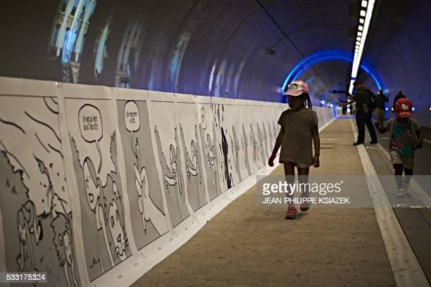 A child walks along a comic strip displayed along the tunnel of CroixRousse in Lyon on May 21 2016 This 16 kilometer fresco realized by 200 French...