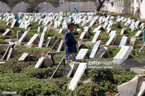 A child walks among graves of people who were killed in the ongoing war including children killed by airstrikes at a cemetery on October 12 2018 in...