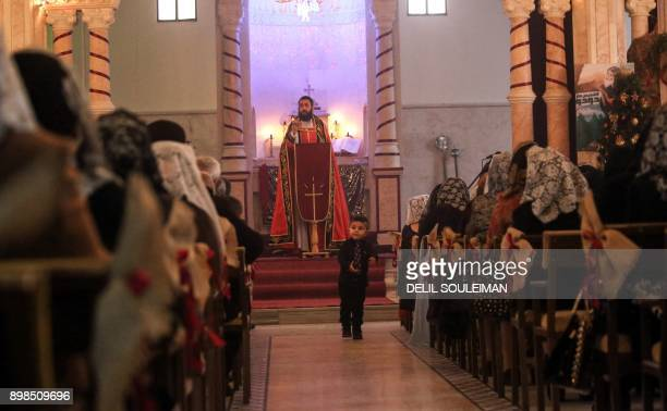 A child walks as a Syriac Orthodox priest speaks during Christmas day mass at the Church of Mar Dodo in the northeastern Syrian Kurdish town of Derik...