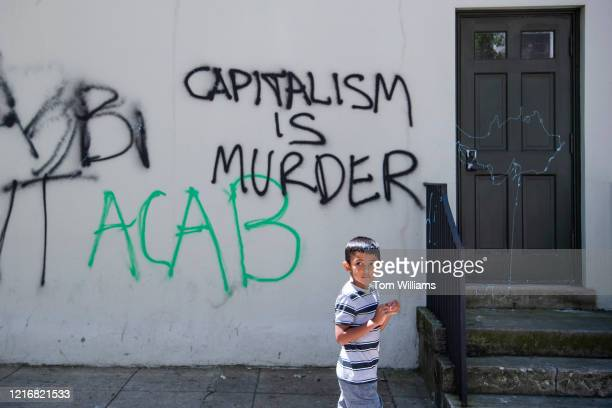 Child walks by graffiti on H St. NW, on Monday, June 1 after weekend protests sparked by the death of George Floyd occurred near the White House.