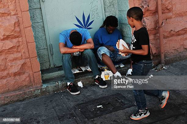 A child walks by two men who are high on K2 or 'Spice' a synthetic marijuana drug along a street in East Harlem on August 28 2015 in New York City...