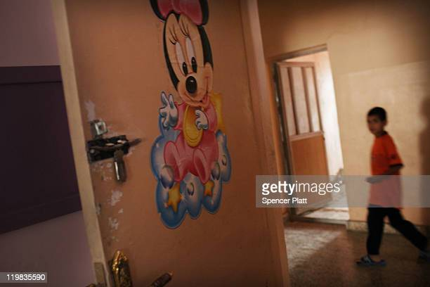 Child walks down the hall at the Al-Baraum orphanage on July 25, 2011 in Baghdad, Iraq. The state owned orphanage has about 50 children currently...