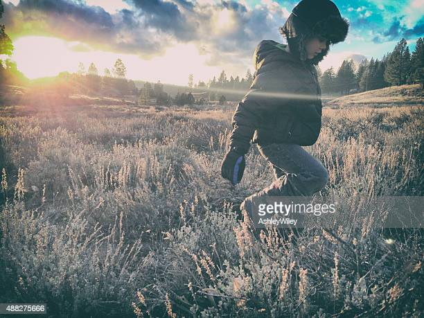 Child walks in a dry wild field at sunset in winter