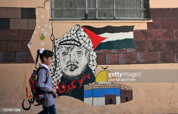 TOPSHOT A child walks in front of a mural painting depicting the late Palestinian leader Yasser Arafat on her way to a school run by United Nations...