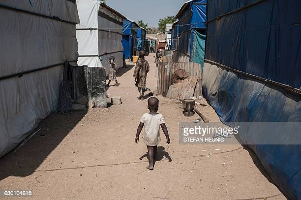 A child walks in the aisle of the Internally Displaced People camp in Bama on December 8 2016 The houses are burntout shells and charred cars and...