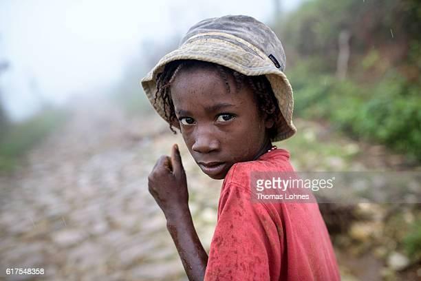 A child walks in the rain on October 17 2016 in Despagne near Jeremie Haiti The hurricane Matthew had heavily devastated the southern half of HaitiÊ...