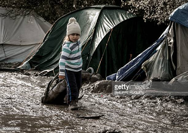 TOPSHOT A child walks in the socalled 'Jungle' migrant camp in GandeSynthe where 2500 refugees from Kurdistan Iraq and Syria live on February 11 2016...