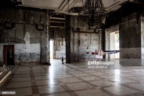 TOPSHOT A child walks inside the hall of the derelict Bamboo Palace of former president of the Democratic Republic of the Congo Mobutu Sese Seko on...