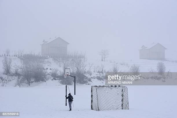 TOPSHOT A child walks on a soccer field covered with snow near the village of Kllokot on January 24 as the country continues to experience subzero...