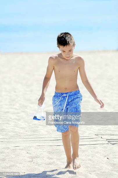 Child walks on beach under sun