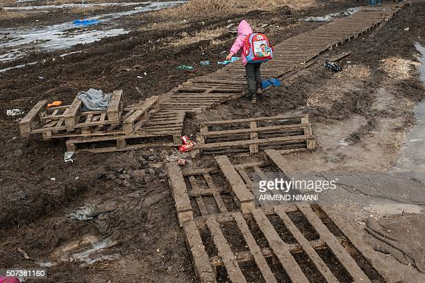 A child walks on wooden palletss after crossing the Macedonian border into Serbia with other migrants and refugees near the village of Miratovac on...