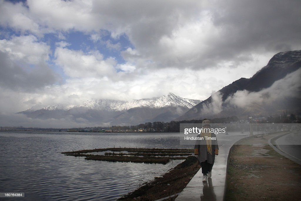 A child walks over the parapet washed by morning rain lining the banks of Dal Lake, on February 5, 2013 in Srinagar, India. Since Sunday night, Kashmir has been lashed with intermittent snow and rain which weather office predicted will continue for two more days.