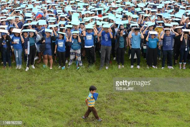 TOPSHOT A child walks past activists gathered for a worldwide climate rally at the University of the Philippines' campus in Manila on September 20...