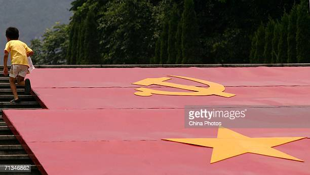 A child walks past billboards featuring flags of the People's Republic of China and the Communist Party of China at the Geleshan Martyrs Cemetery...