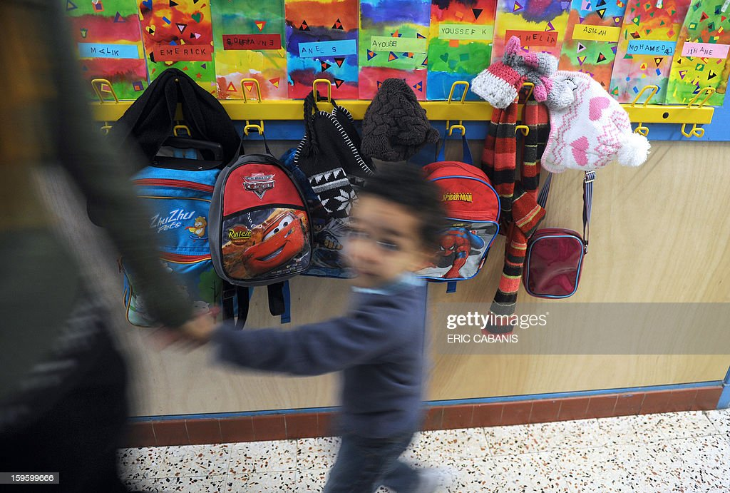 A child walks past schoolbags at the Clement-Falucci school, on January 17, 2013 in Toulouse, southwestern France. French government expects to send to school 30% of toddlers children less than three years before 2015.