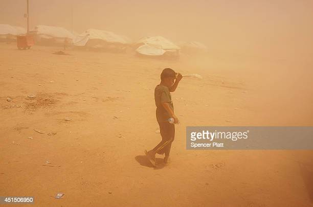 A child walks through a dust storm at the Khazair displacement camp for those caughtup in the fighting in and around the city of Mosul on June 30...