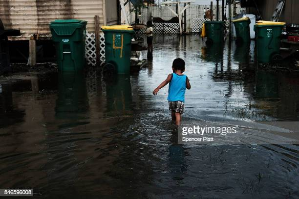 A child walks through flooded streets in the rural migrant worker town of Immokalee which was especially hard hit by Hurricane Irma on September 13...