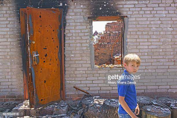 A child walks through the remains of his house amongst the village ruins of Semyonovka on July 11 near the eastern Ukrainian city of Slavyansk...