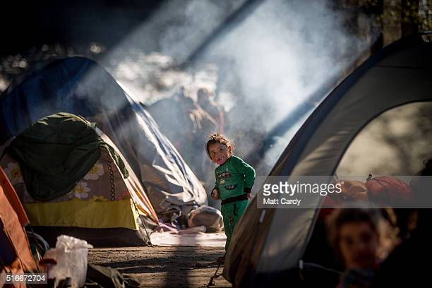 A child wanders between tents erected inside an old railway shed where people are sheltering at the Idomeni refugee camp on the Greek Macedonia...