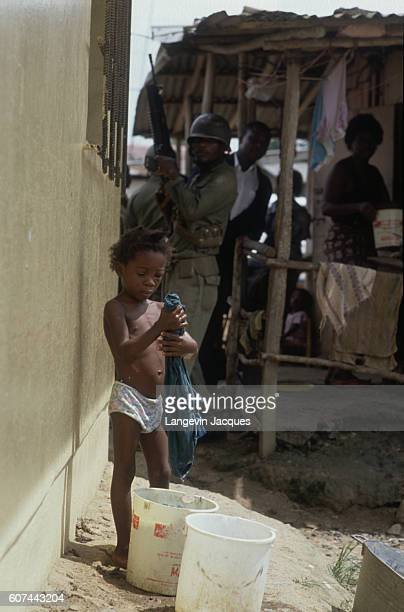 A child washes clothes in a bucket seemingly oblivious to armed soldiers nearby Liberian Army troops control the international airport and the...