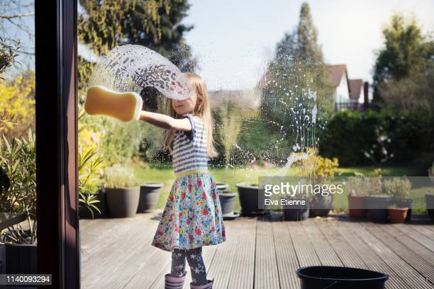 child (6-7) washing patio window with sponge and soapy water, outside on a sunny day - きれいにする ストックフォトと画像