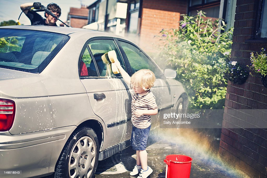 Child washing the car with daddy : Stock Photo