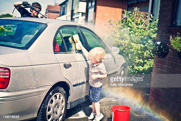 Child washing the car with daddy