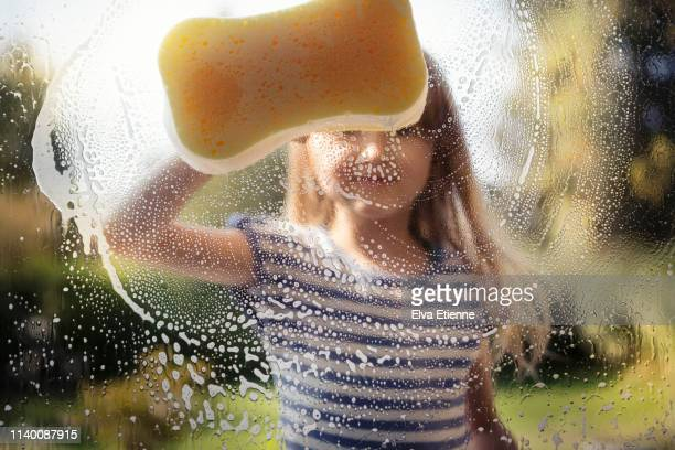 child (6-7) washing window with sponge and soapy water, outside on a sunny day - hausarbeit stock-fotos und bilder