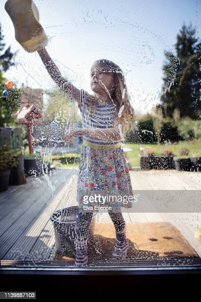 child (6-7) washing windows with sponge and soapy water, outside on a sunny day - somente crianças - fotografias e filmes do acervo