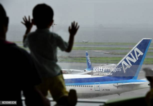 A child watches All Nippon Airways jetliners on the tarmac at Haneda international airport in Tokyo on August 2 2017 Japan's All Nippon Airways is...