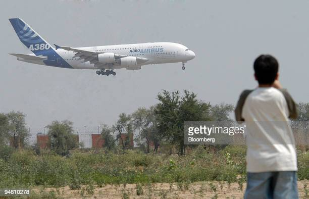 A child watches an Airbus A380 super jumbo passenger plane land during its first visit to Indira Gandhi International Airport in New Delhi India on...